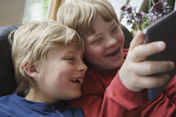 Close-up of happy brothers using digital tablet at home