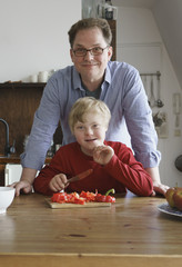 Portrait of father and boy at table in kitchen