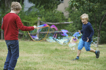 Happy brothers playing with soap bubble in back yard
