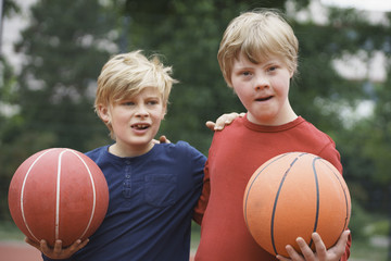 Brothers standing arms around while holding basketballs in park