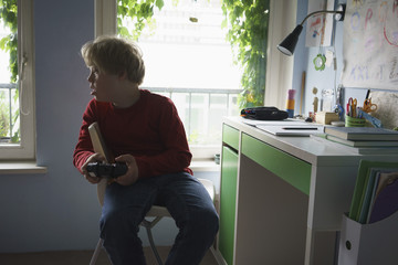 Disabled boy playing video game while sitting on chair in room