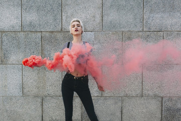 Confident young woman standing with distress flare against wall