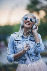 Happy fashionable woman wearing sunglasses while listening to music through headphones