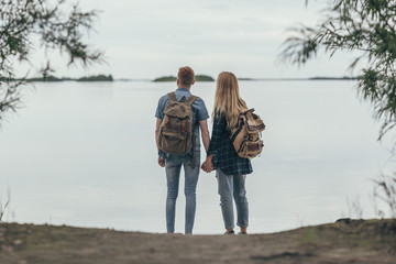 Rear view of couple holding hands while standing on lakeshore