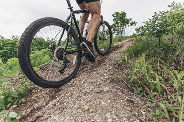 Low section of man riding mountain bike on dirt track