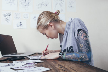 Confident tattoo artist working on designs by laptop at art studio