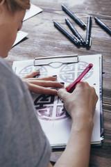 Tattoo artist drawing designs at table in art studio