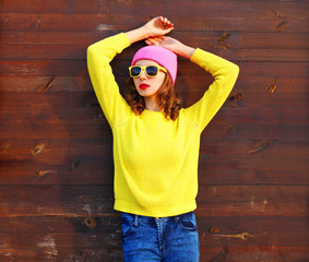 Portrait fashion cool girl in colorful clothes over wooden backg