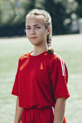 Portrait of confident teenage soccer player standing on field