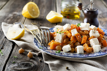 Warm salad of pumpkin, chickpeas and feta cheese on the old wooden background. Selective focus.