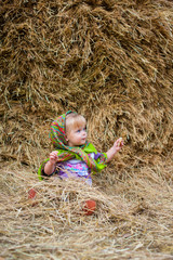 Close up image of beautiful little girl in russian village traditional kerchief with round cracknel  over autumn weather