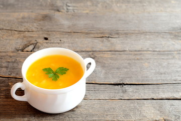 Pumpkin soup in bowl isolated on old wooden background with blank space for text. Simple pumpkin soup recipe. Vegetable dish
