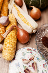 corn and pumpkin on a wooden table with onions