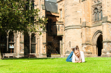Young cheerful girl lying on the grass  in Glasgow University ga