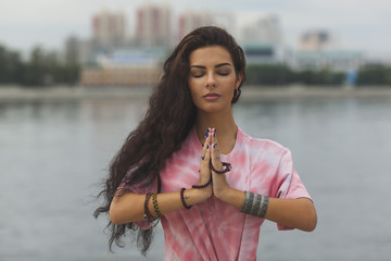 Woman with closed eyes meditating in prayer position against river