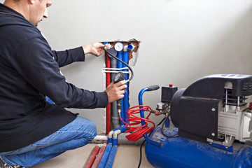 Plumber tests for leaks. Plumber fixing central heating system.