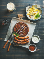 Grilled sausages with sauces, roasted potato and glass of dark beer on rustic wooden serving board over dark scorched wooden background, top view