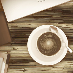 Overhead view of white cup of coffee on a wooden cafe table.