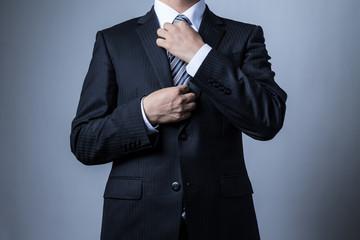 スーツを着ているビジネスマン、ネクタイをしめる