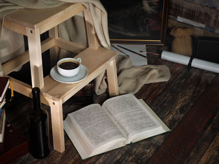 Cozy Corner studio of an artist. Wooden stand, a cup of coffee, a picture in a frame, different interior details and objects. Open book