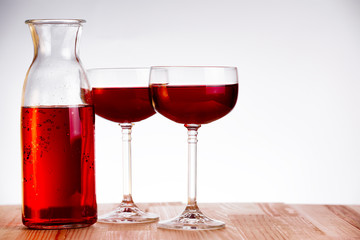 Two glass and carafe of wine on natural wooden table.