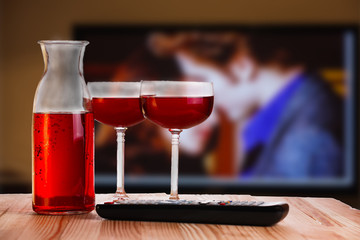 Two glass and carafe of wine with TV remote.