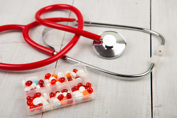 Stethoscope and pills in container on the wooden desk