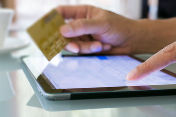 Man using a credit card and tablet for buying on-line