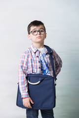 serious child boy with shoulder bag and wearing glasses