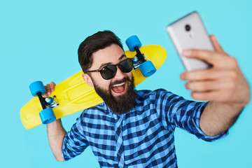 Modern teenage guy taking a self portrait over colorful background