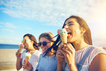 Three young woman eating ice cream at the seaside