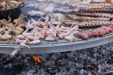 Cooking outdoors. Traditional food of Spain. Big barbecue grill. Ribs, chorizo and chicken. Medieval market.