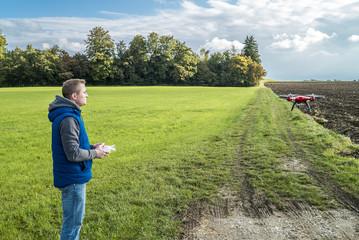 Junger Mann steuert seine Drohne zwischen Acker und grüner Wiese
