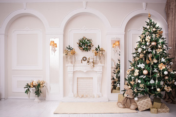 Majestic white hall with classical fireplace, arches and mirrors. At the wall Christmas wreath. New Year tree stands in the corner of room.