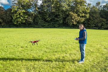 Mann fliegt seinen Quadrocopter über eine grüne Wiese