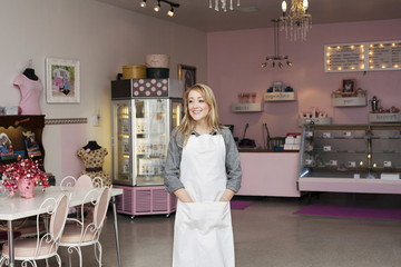 Owner looking away while standing in cake shop