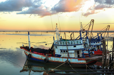 Fishing boats at port with sunset