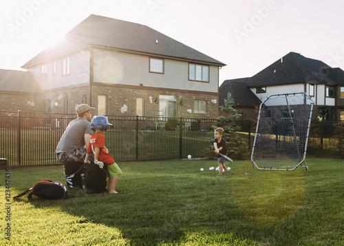 Sunny Day Backyard Baseball : Family playing baseball at backyard on sunny day Stock photo and