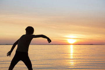 Rear view of boy skipping stone at beach during sunset