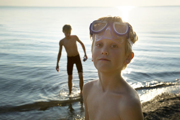 Portrait of boy wearing swimming goggles on shore with friend in background