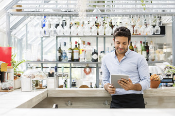 Bartender using tablet computer at counter in restaurant