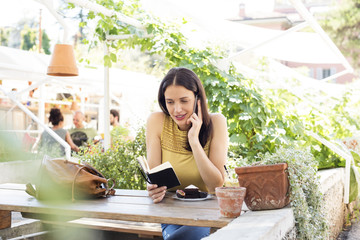 Woman reading diary while using smart phone at sidewalk cafe