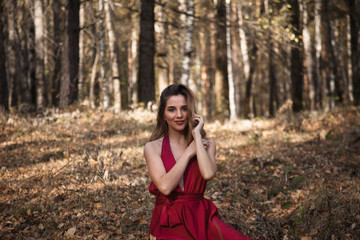 beautiful girl in a red dress in the forest