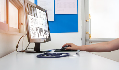Doctor working with computer pc at desk in the hospital