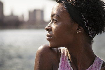 Close-up of thoughtful woman against river in city