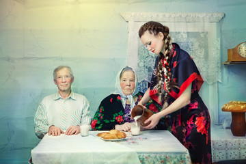 Woman wearing patterned dress with couple at table