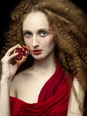 Woman with long crimped hair eating pomegranate