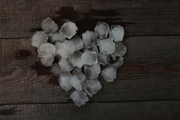 a heart of ice cubes laid on wooden background