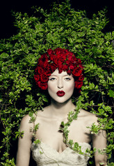 Young woman wearing red flowered headdress pouting in front of ivy plants