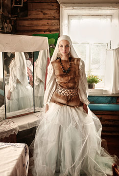Woman wearing white tulle dress and fur vest